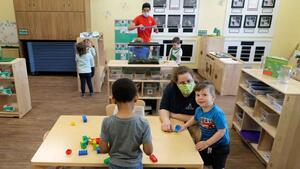In this May 27, 2020, photo, teachers Jana Blair, right, and Aaron Rainboth, upper-center, wear masks as they work with kids at the Frederickson KinderCare daycare center, in Tacoma, Wash.